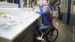 Photo: Wheelchair user in a production hall at a drawing table; Copyright: O4 Wheelchairs GmbH