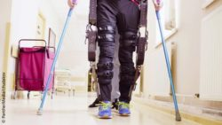 Image: A person with crutches and an exoskeleton is walking along a hospital hallway; Copyright: PantherMedia/chudakov