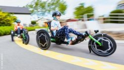 Photo: A girl and a boy ride the TRETS trikes one behind the other. The background is motion blurred, which gives the impression of speed; Copyright: HASE BIKES