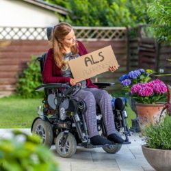"Photo: Woman in wheelchair - Bianca Riedmann - holding a cardboard sign with the words ""ALS Awareness""; Copyright: private"