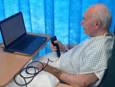 Photo: Man in hospital bed with laptop