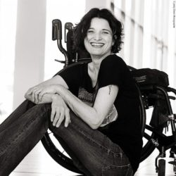 Photo: Sabine Klemens is sitting on the floor and smiles at the camera; Copyright: Jenny Klestil Photographie