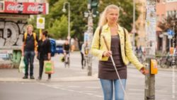 Photo: Blind woman with a white cane standing at the traffic lights; Copyright: visitBerlin, Andi Weiland | Gesellschaftsbilder.de