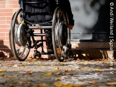 Photo: Wheelchair user facing an entrance with stairs