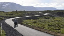 Photo: A wheelchair user on an winding road in Iceland; Copyright: RUNA REISEN GmbH