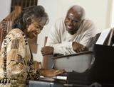 Photo: Elderly woman playing the piano, man next to her smiles