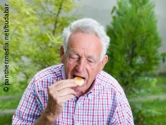 Photo: Elderly man eats some bread