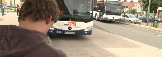 "Photo: Man in front of a bus - linked to video ""Mobility – accessible travel with public transportation""; © REHACARE.com"