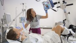 Photo: Researcher with a ICU patient doing bicycle exercise in bed; Copyright: Marta Hewson/Photography
