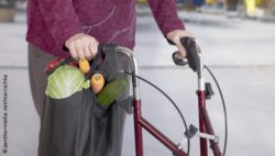Photo: Elderly woman with a wheeled walker aid and holding a shopping bag in her hand; Copyright: panthermedia.net/marischka