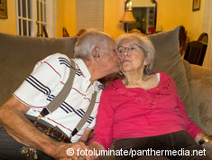 Photo: Elderly man kisses his wife