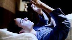 Photo: Man using his phone in the bed because of sleeping problems; Copyright: panthermedia.net/minervastock