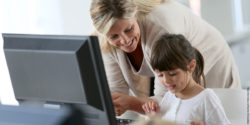 Photo: Teacher standing behind a girl who sits at a computer; Copyright: panthermedia.net/Fabrice Michaudeau