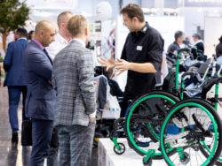 Photo: Several trade visitors in suits talk to each other at REHACARE