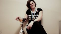 Photo: Katrin Neudolt sits next to a trophy and wears a medal around her neck; Copyright: private