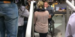 Photo: Interview situation with a wheelchair user in front of a camera; Copyright: beta-web/Lormis