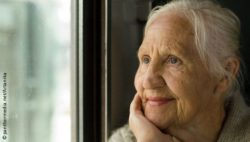 Photo: Elderly woman looking out of a window and smiling; Copyright: panthermedia.net/Artanika