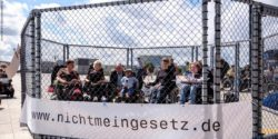 Photo: Many people with disabilities in a huge cage - during a protest event; Copyright: Andi Weiland | Gesellschaftsbilder.de