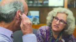 Photo: An older adult trying on a hearing aid; Copyright: Baycrest