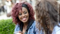 Photo: Young woman smiles while talking to another woman; Copyright: panthermedia.net/javiindy