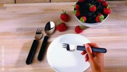 Image: Hand holds a fork, ergonomically contoured utensils and strawberrys behind; Copyright: etac GmbH