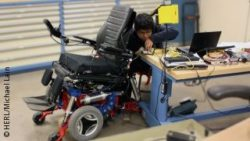 Photo: Young engineer is working at a wheelchair in a lab; Copyright: HERL/Michael Lain