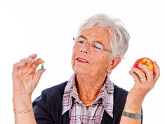Photo: Elderly woman with an apple and a pill
