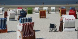 Photo: A lot of beach chairs, in between a wheelchair at the beach; Copyright: panthermedia.net/Antje Lindert-Rottke