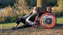 Photo: Richard J. Schaefer sitting under a tree, next to him you can see his wheelchair; Copyright: DieFotoFrau