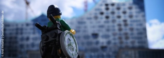 Photo: A wheelchair user as a Lego figure in front of the Hamburg Elbphilharmonie; Copyright: Andi Weiland | Gesellschaftsbilder.de