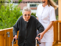 Photo: Elderly woman with wheeled walker and a caregiver