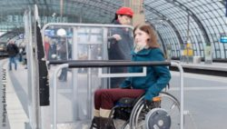 Photo: A wheelchair user in a boarding aid for the train; Copyright: Wolfgang Bellwinkel | DGUV