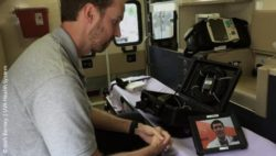 Photo: Paramedic sits in an ambulance talking with a doctor via tablet; Copyright: Josh Barney | UVA Health System
