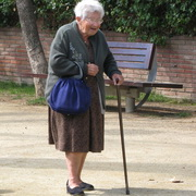 Photo: An old woman walking with a crooked stick