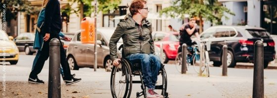 Photo: Wheelchair user sitting at a street and looking to his left; Copyright: visitBerlin, Andi Weiland l Gesellschaftsbilder