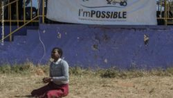 Photo: Afro-american child sitting in front of an imPOSSIBLE sign; Copyright: Amos Gumulira/Agitos Foundation