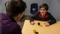 Image: A young boy with brown hair is sitting across the table from a young man. Between them, there are colored square blocks; Copyright: MU Thompson Center for Autism and Neurodevelopmental Disorder