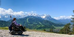 Photo: Woman in power wheelchair X8 in the mountains, in the background the mountain panorama of the Zugspitze; Copyright: Sunrise Medical