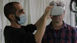 Photo: a man with dark hair and mask is helping an older man with white hair putting on a virtual reality headset; Copyright: University of Bath