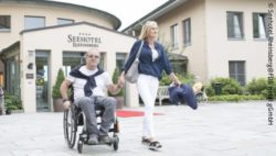 Photo: Man in wheelchair with his wife in front of a hotel entrance; Copyright: Seehotel Rheinsberg@FDS Hotel gGmbH