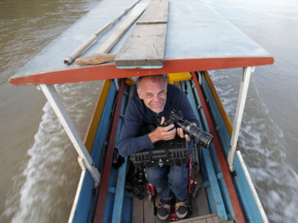 Photo: Andreas Pröve with a camera on a small boat
