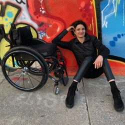 Photo: Sabine Klemens in a Kinetic Balance outfit, sitting on the floor in front of a graffiti wall, next to her the wheelchair; Copyright: Christoph Klemens/Kinetic Balance
