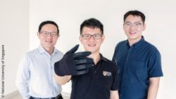 Image: Three researchers are presenting a black glove; Copyright: National University of Singapore