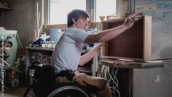 Image: A young man in a wheelchair is working on a wooden drawer in a carpenter's shop; Copyright: Andi Weiland | Gesellschaftsbeilder.de