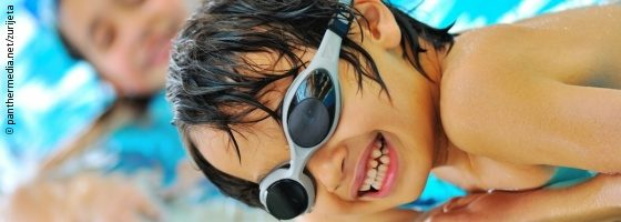 Photo: Young boy at the edge of a swimming pool smiling into the camera; Copyright: panthermedia.net/zurijeta
