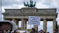 "Photo: A demonstrator holding up a sign saying: ""we are also voters"" in front of the Brandenburg Gate in Germany; Copyright: Andi Weiland 