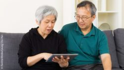 Photo: Two elderly Japanese people using a tablet; Copyright: PantherMedia/Leung Cho Pan