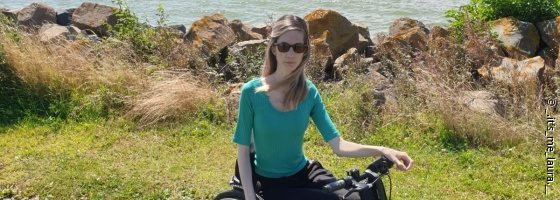 Photo: woman with a turquoise shirt in a black wheelchair, sea in the back - Laura W.; Copyright: _.it's_me_laura.__