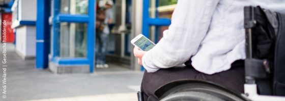 Photo: A wheelchair user stands in front of an elevator and holds a smartphone in her hand, on which an app displays elevator problems; Copyright: Andi Weiland | Gesellschaftsbilder.de