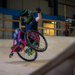 Photo: a woman with a helmet – Lily Rice – is doing a stunt with her pink wheelchair, she's doing a wheelie where her wheelchair is only standing on one wheel; Copyright: Steven Clarey